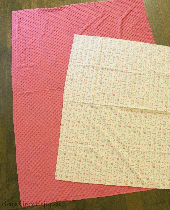 Two pieces of fabric. One white flannel with words the other pink minky dot.