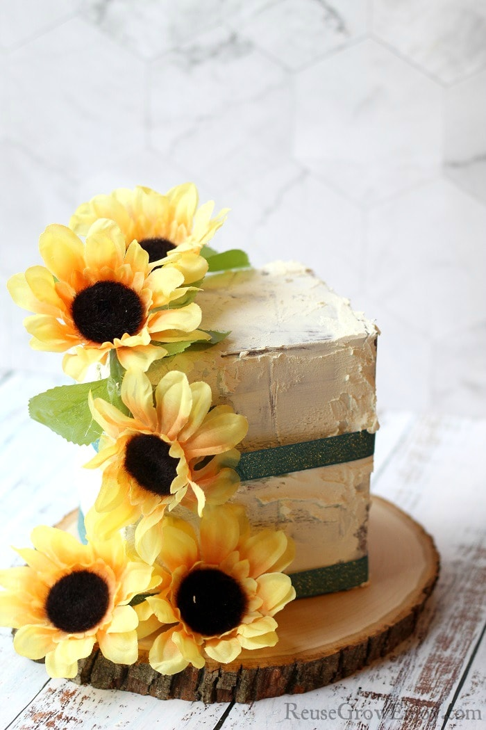 A finished fake cake prop with sunflowers and green ribbon. It is on a wood slice.