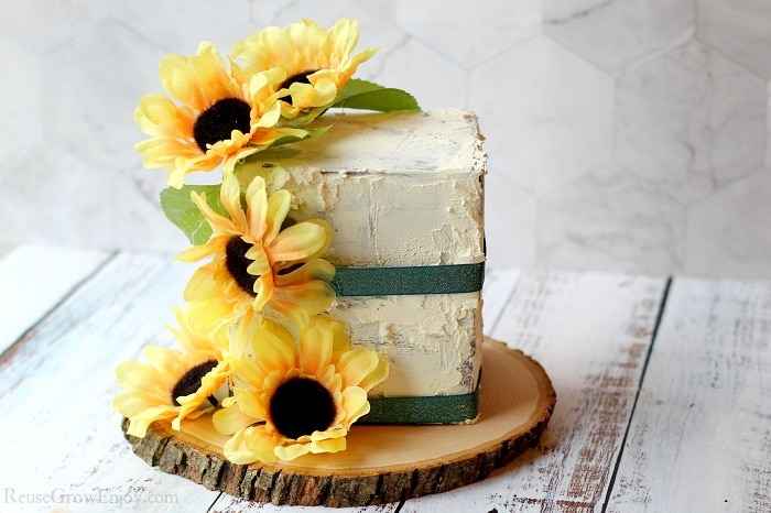 Finished fake cake prop with sunflowers on a wood slice. Laying on white wood background.