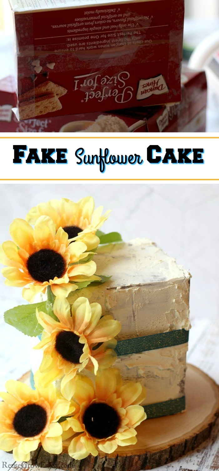 "A finished fake cake prop with sunflowers and green ribbon. It is on a wood slice at bottom. Top is boxes used to make it. Text overlay that says ""Fake Sunflower Cake""."