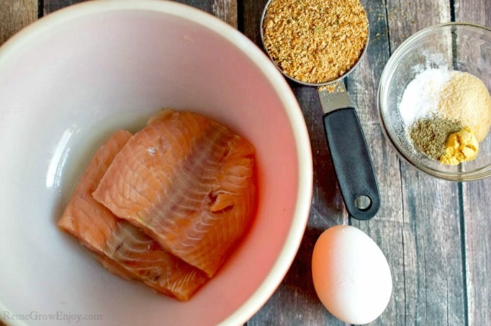 Two pieces of salmon in a bowl, one white egg, a scoop of bread crumbs and a small clear bowl with spices all laying on wood background