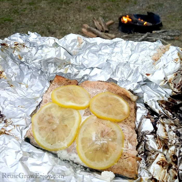campfire cooked salmon on foil with lemon slices. Campfire in background.