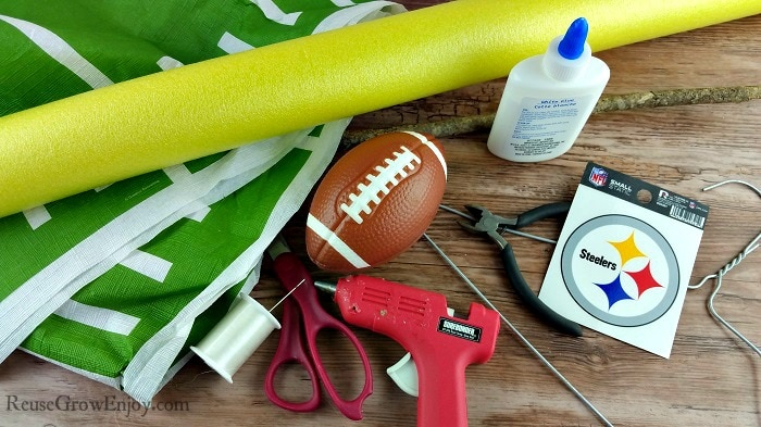 Supplies needed to make this football decor, picture includes things like yellow pool noodle, hot glue gun and foam football to name a few.