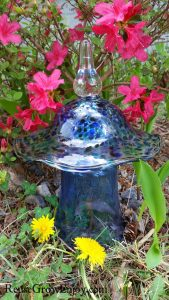 Blue with blue flecks glass garden ornament mushroom made from upcycled glass and candy dish top sitting in front of pink flowers.