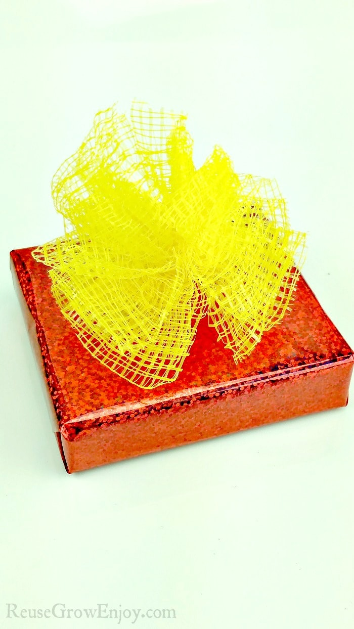 Red wrapped gift with yellow mesh produce bags made into bow on top.