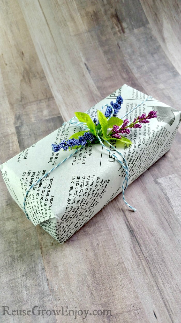 Small gift wrapped in newspaper with flowers on top.