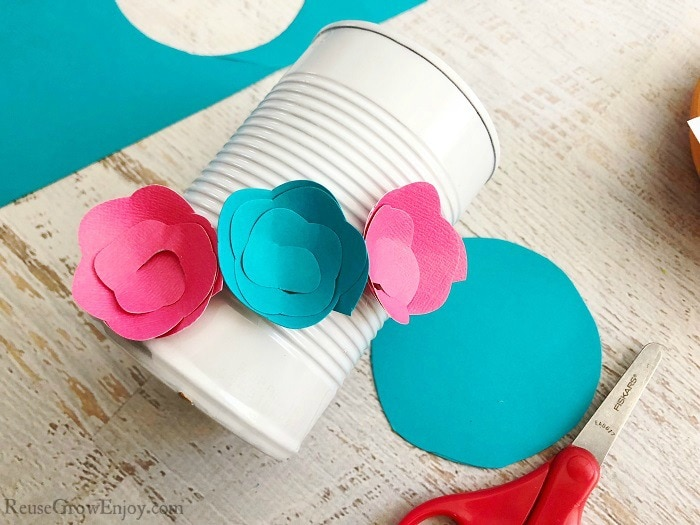 Pink and blue paper flowers being attached to white can.