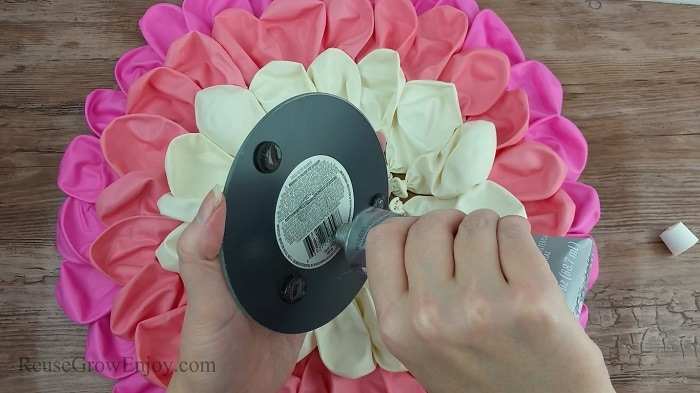Hand gluing mirror in center of balloons.