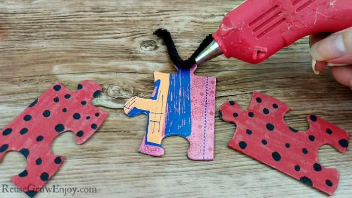 Glue pipe cleaner to back of black puzzle piece