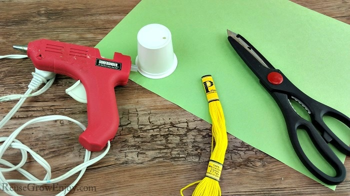 Hot glue gun, yellow string, empty clean k-cup, scissors and green paper.