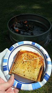 Grilled Cheese on plate with campfire in background.