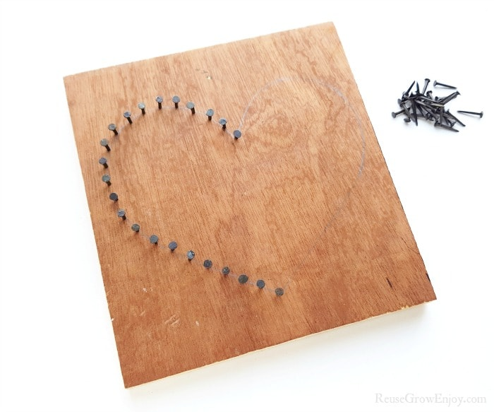 Nails being hammered into a heart shape on wood.