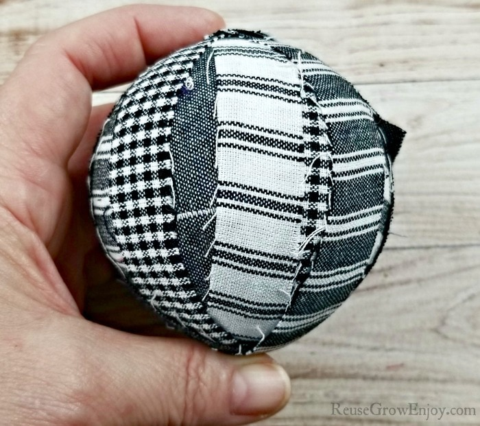 Hand holding ball covered in fabric strips