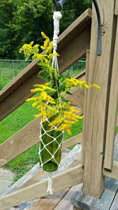 Hanging Wine Bottle Vase on a deck with yellow flowers in bottle