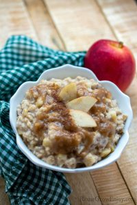 White bowl with homemade caramel apple oatmeal on wood background with cloth napkin and fresh red apple.