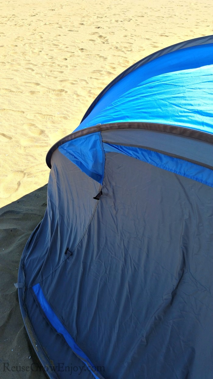 Blue tent set up on sand with nothing but sand behind it.