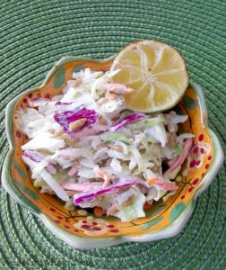 A flower shaped bowl on a light green placemat full of homemade coleslaw with a slice of lemon on the upper right of the bowl.