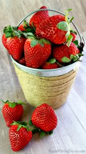 Small tin bucket wrapped in twine filled with fresh strawberries. The fresh strawberries in front of the bucket laying on a wood background.
