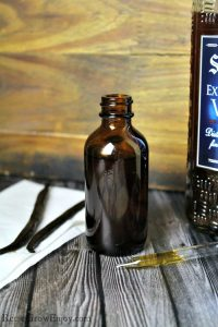 Small brown bottle full of homemade vanilla extract with vanilla beans on the left side.