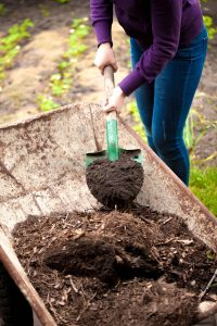 Person mixing compost in wheelbarrow