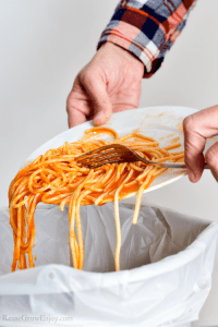 Plate of pasta being scraped into the trash