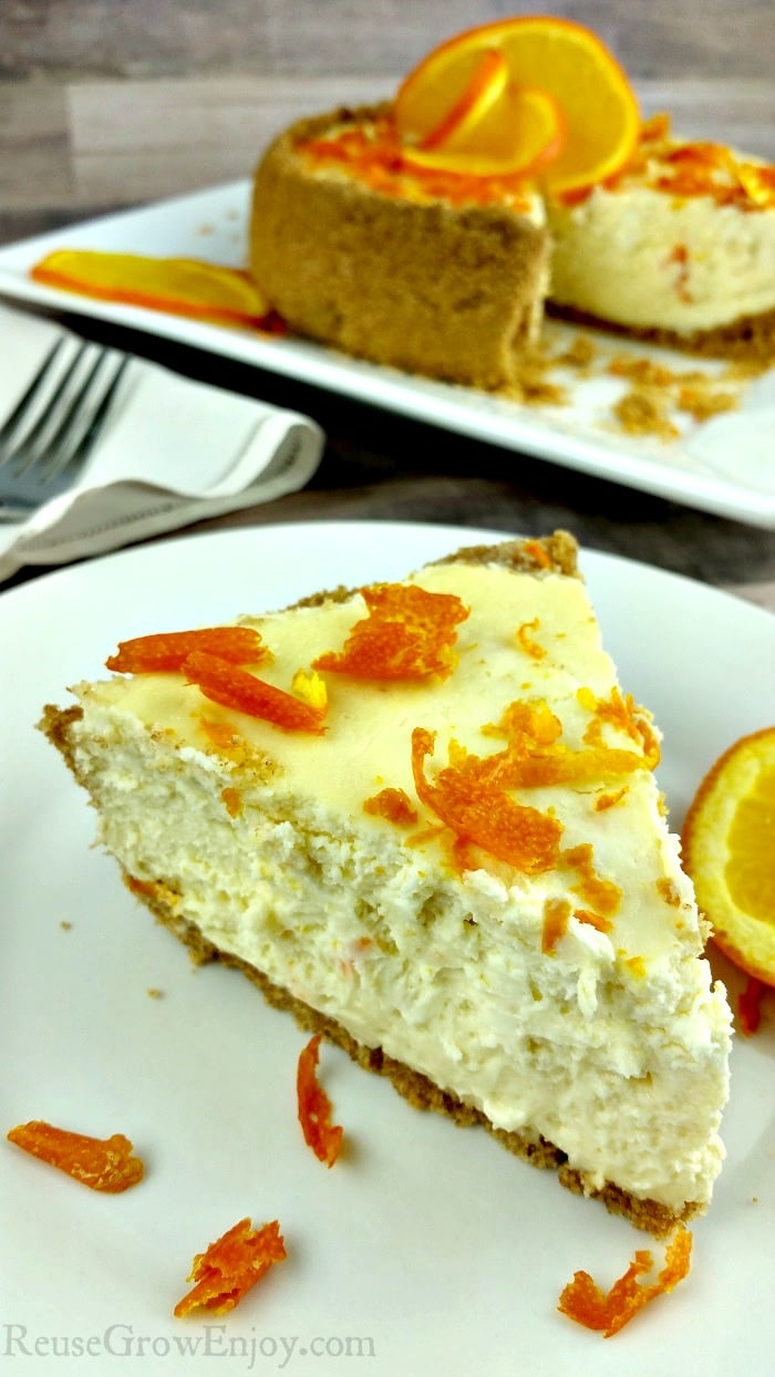 Slice of orange Instant Pot cheesecake in front on a white plate with orange zest as garnish. In the background is the rest of the whole cheesecake.
