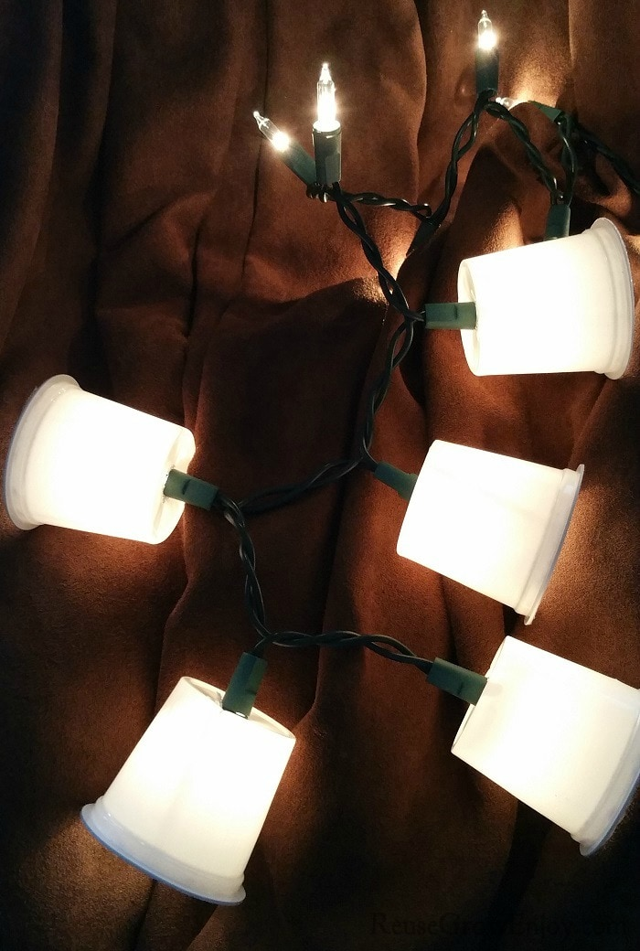 Dark brown background with small lights that have k-cups over them and are lighted.