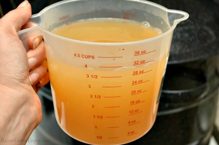 Large measuring cup full of the strained liquid from the loquat fruit.