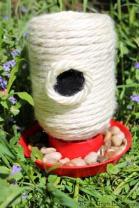 Finished bee feeder sitting in grass and purple flowers