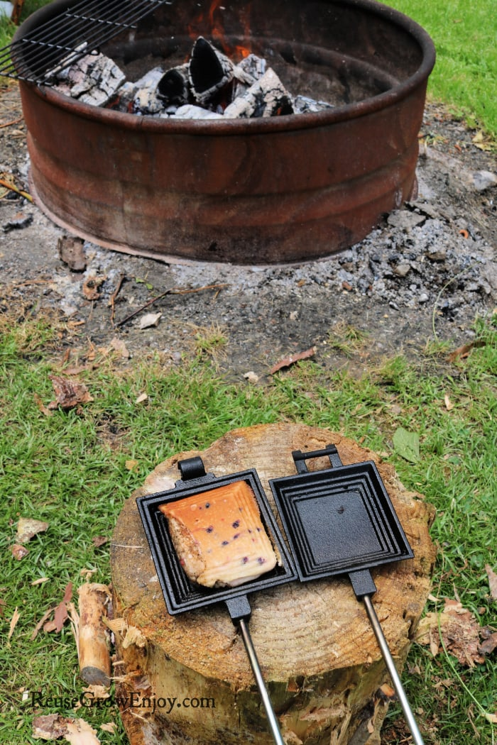 Muffin in pie iron on a stump with campfire in background
