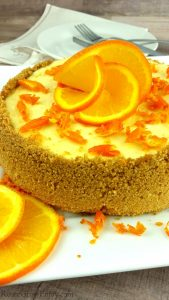 A whole orange cheesecake on a white plate with orange slices that look like a flower on the top.