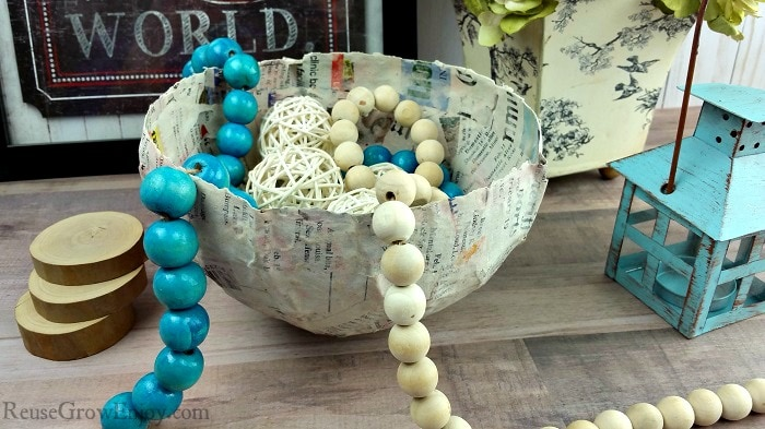 Finished paper mache bowl with farm beads and wicker balls inside. Picture and flowers in background and small teal tealight on the right side.