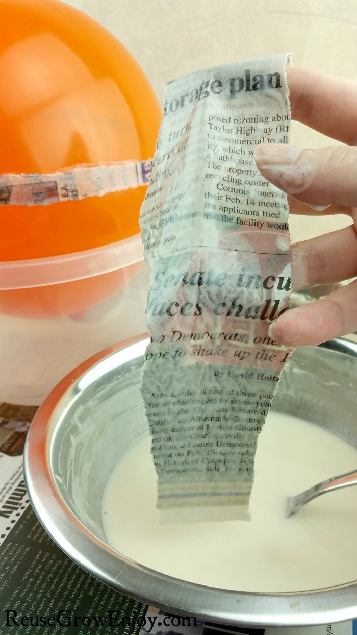 Hand dipping strips of newspaper in paper mache paste with partly covered balloon in background.
