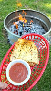Pepperoni grilled cheese in red basket with a dish or red dipping sauce. Campfire in background.