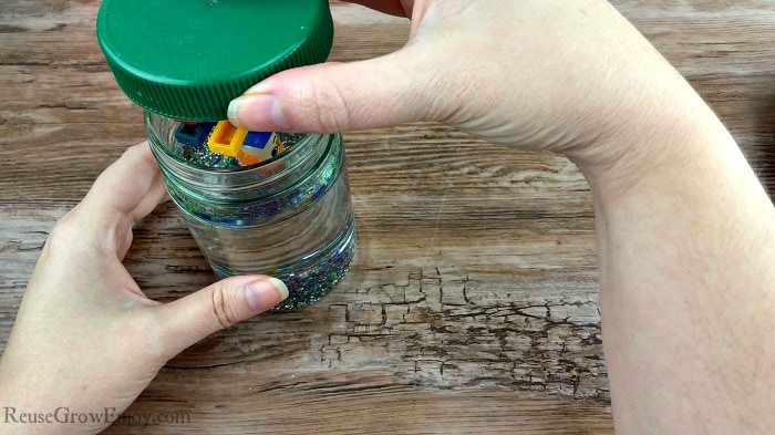 Hand placing top with glued on LEGO's into oil filled jar.
