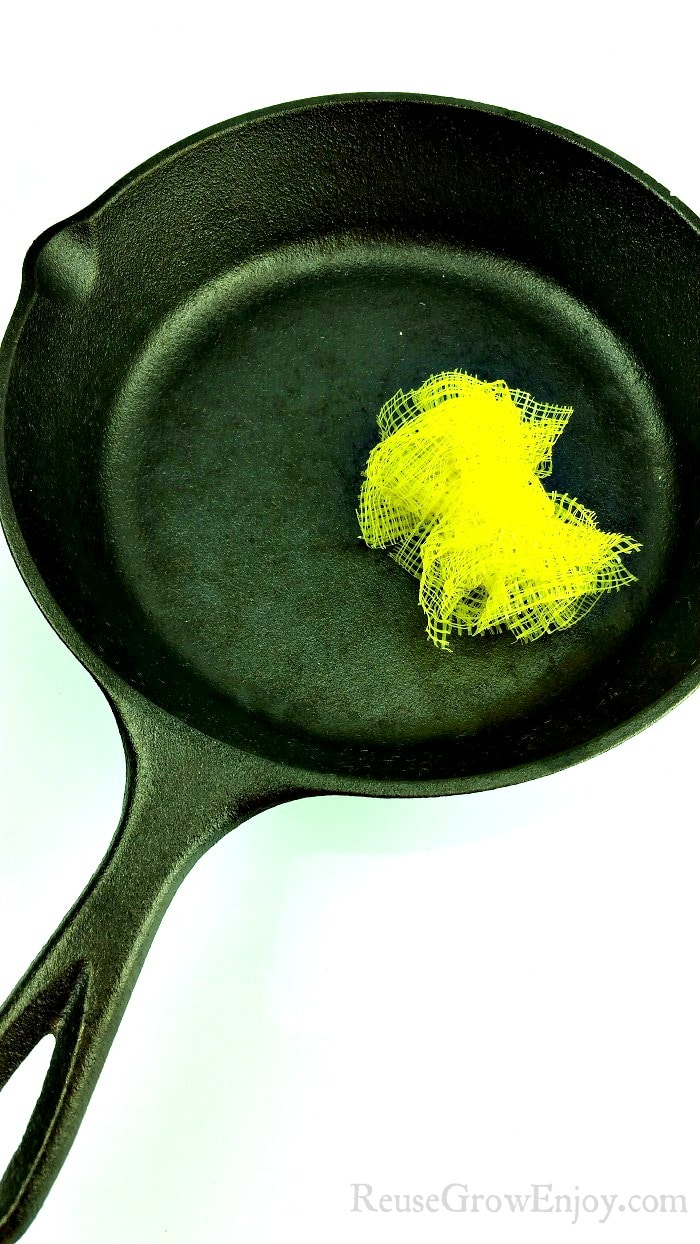 Black cast iron pan with yellow mesh produce bags made into scrubber laying in pan