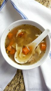 Homemade chicken soup with carrots in white bowl with white soup spoon. Bowl is sitting on a white kitchen towel with a blue stripe on a granite counter.