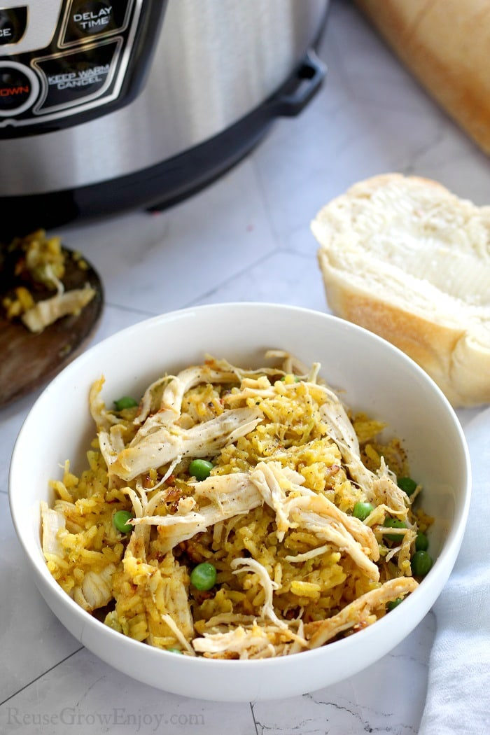 Cooked chicken and yellow rice in a white bowl with a piece of butter bread to the right side and a pressure cooker in the background on the left side.