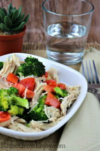 White plate with lemon pepper chicken with broccoli and tomatoes on it with a glass of water in background.