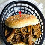 Pulled pork sandwich on a bun sitting in a black plastic basket with a cloth napkin under it and a wood background.