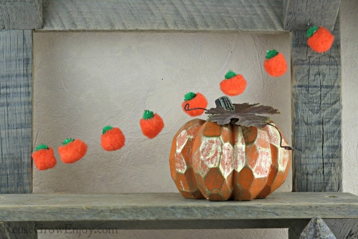 Finished pumpkin fall garland hanging on barn wood shelf with pumpkin decor in front.