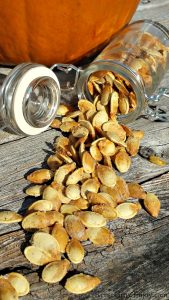 Glass jar on its side spilling out with roasted pumpkin seeds with a pumpkin in the background. Pumpkin seeds are coated in salt and pepper from the pumpkin seed recipe