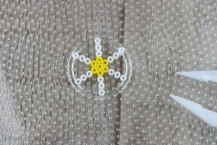 Put lines of white beads on side of yellow