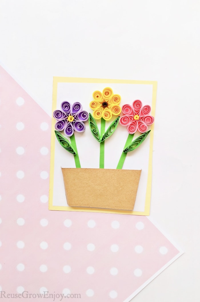 Quilled flowers on paper making a card
