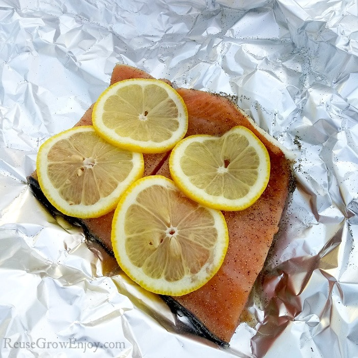 Raw salmon on foil with slices of lemon.