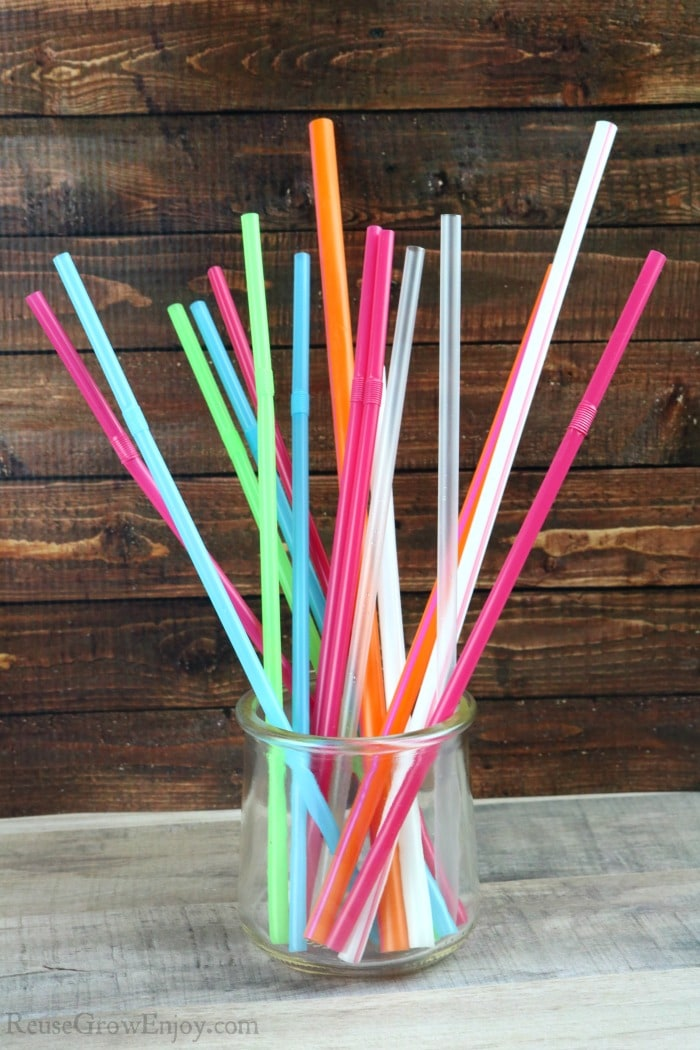 Glass jar full of all different colors and sizes of plastic straws