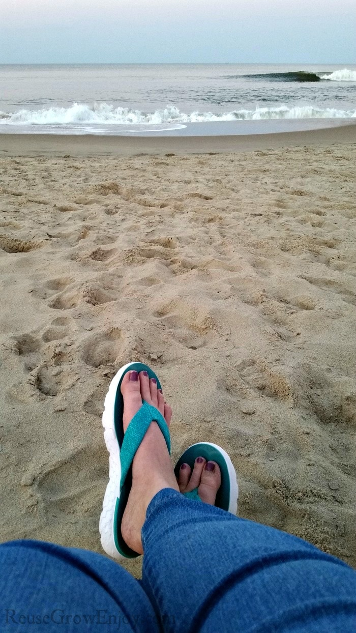 Womens legs in jeans and flip flops crossed with sand and ocean in background.