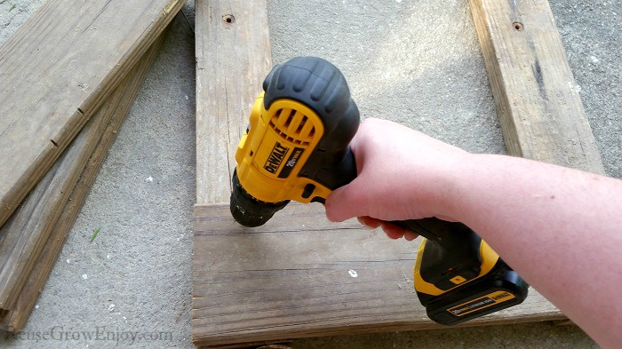 Hand with DeWalt drill attaching boards to 2x4's.
