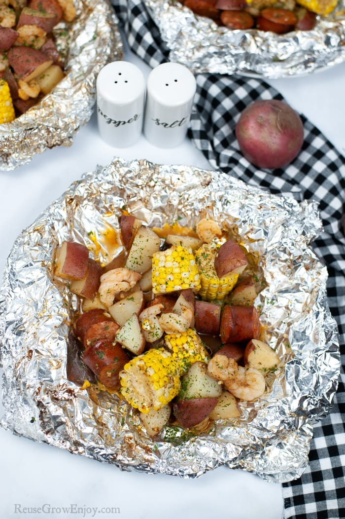 Shrimp Boil Foil Pouch Dinner opened up on table with two more in background