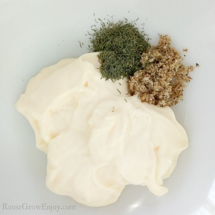 A bowl with mayo, dried dill and lemon pepper seasoning mix